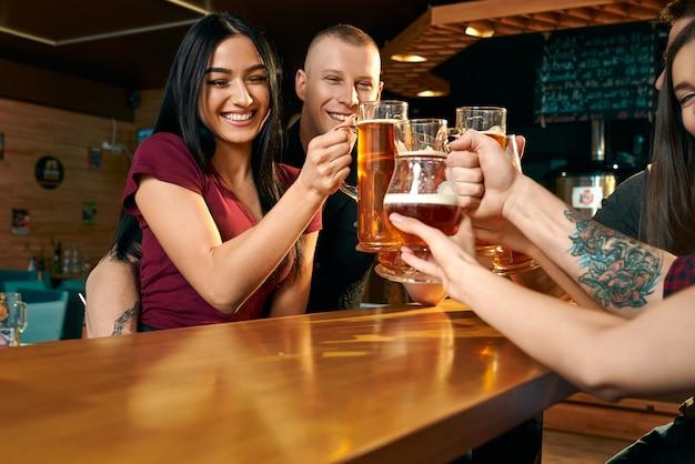 Vista dal lato della donna felice e dell'uomo che si abbracciano e brindano con gli amici nel pub