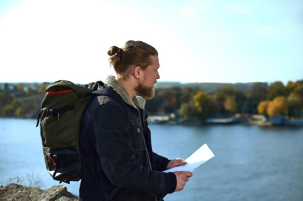 Vista dal lato di un viaggiatore uomo con zaino in possesso di una mappa del percorso sul bordo della scogliera e ammirando la bellezza della natura. un bellissimo paesaggio autunnale e lago