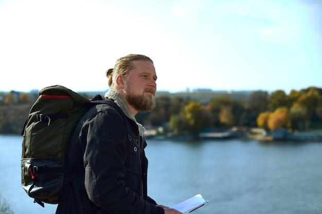 Vista dal lato di un viaggiatore uomo con zaino in possesso di una mappa del percorso sul bordo della scogliera e ammirando la bellezza della natura .. concetto di persone che viaggiano nella natura.