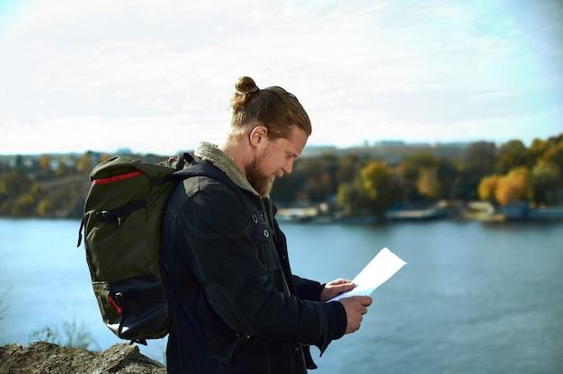 Vista dal lato di un uomo viaggiatore con zaino guardando la mappa del percorso sul bordo della scogliera. un bellissimo paesaggio autunnale e lago