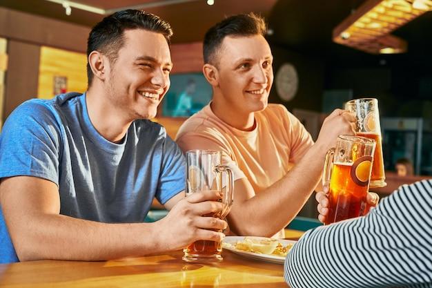 Vista dal lato di due uomini felici che riposano con gli amici al bar, bevendo birra e ridendo insieme. maschio allegro che si guarda l'un l'altro, scherzando e parlando nei fine settimana. concetto di svago e divertimento.
