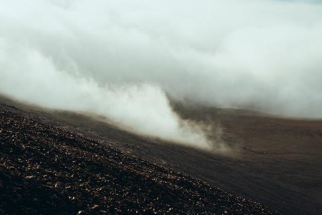Vista dal fianco di una montagna pietrosa alla valle dell'altopiano dentro le nuvole. atmosferico paesaggio alpino minimalista più scuro con nuvole basse nella valle di montagna. splendido scenario montano con fitte nuvole sul terreno
