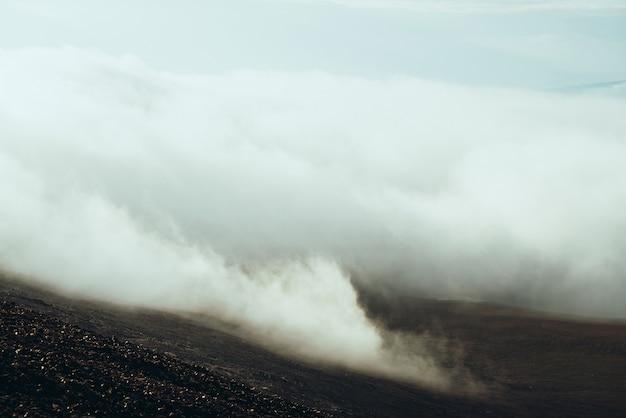 Vista dal fianco di una montagna pietrosa alla valle dell'altopiano tra le nuvole. atmosferico paesaggio alpino minimalista più scuro con nuvole basse nella valle di montagna. meraviglioso scenario di montagna con spesse nuvole a terra