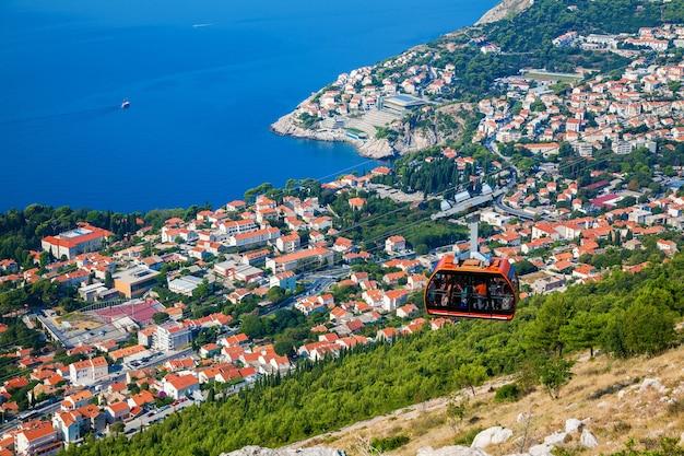 Vista dalla cima del monte srdj alla città di dubrovnik con una funivia che scende, croazia