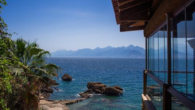 Vista dalla finestra sulle montagne, mare, spiaggia e palme