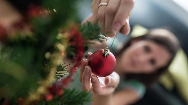Vista dall'alto di una donna che mette una pallina rossa per le vacanze sull'albero di natale con particolare attenzione alla palla.