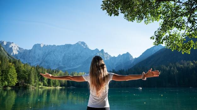 Vista da dietro di una giovane donna con lunghi capelli castani in piedi vicino a un bellissimo lago verde con le braccia larghe, illuminate dal sole.
