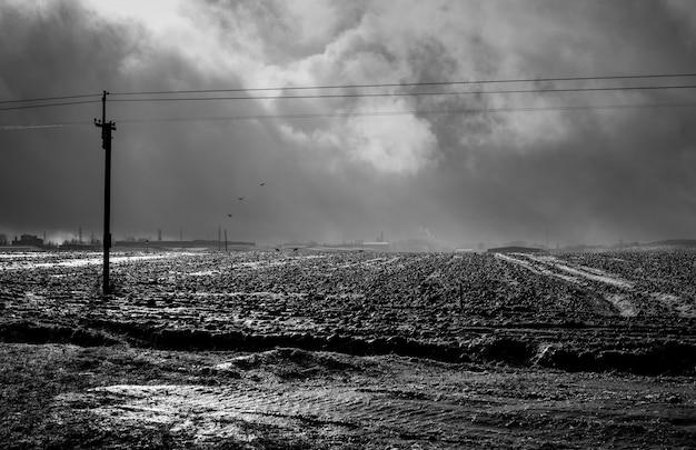 Vista del campo arato ghiacciato, i raggi del sole che si infrangono attraverso le nuvole drammatiche, gli edifici industriali possono essere visti in lontananza. foto in bianco e nero.