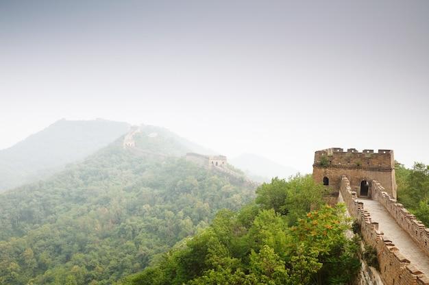 Vista della grande muraglia cinese con la foresta e il cielo verdi.