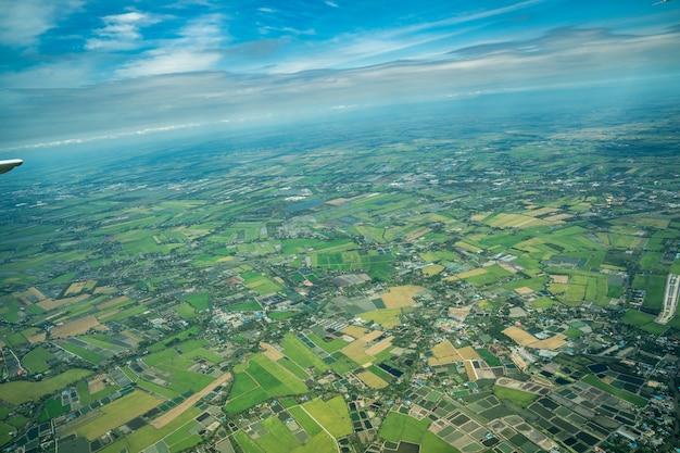 La vista del campo verde e della fattoria e della città nel centro della thailandia. è scattato da jetplane.