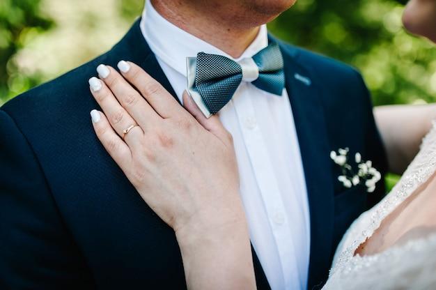 Vista delle mani con fedi nuziali. giorno del matrimonio. ritratto di un attraente sposo abbraccia la sposa