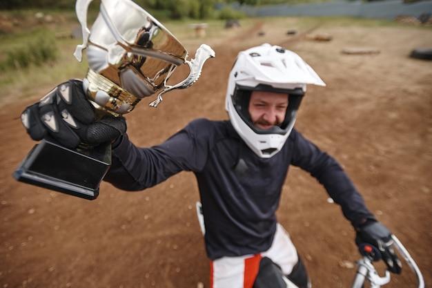 Sopra la vista del motociclista felice in guanti che solleva la mano con la coppa vincente mentre mostra il premio per la competizione su strada