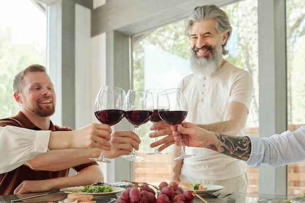 Sopra la vista dei genitori anziani felici e dei loro figli più grandi che tintinnano i bicchieri di vino durante la cena in famiglia