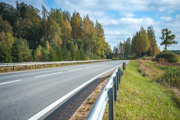 Vista della strada autostrada in autunno. sfondo di viaggio. autostrada asfaltata che passa attraverso la foresta. lettonia. baltico.