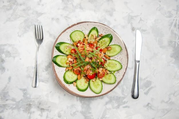 Sopra la vista di una deliziosa insalata vegana fatta in casa decorata con cetrioli tritati in una ciotola posate su superficie bianca macchiata con spazio libero