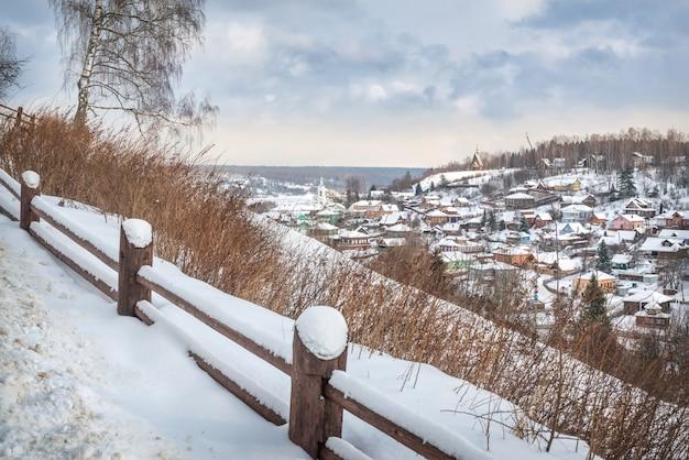 Vista delle case di plyos e della chiesa di varvara in una giornata invernale nevosa