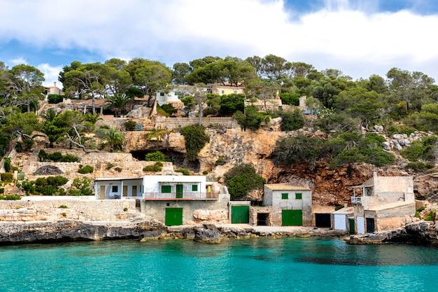 Una vista delle case con i garage della barca e l'acqua di mare azzurrata, cala llombards, isola di mallorca, spagna