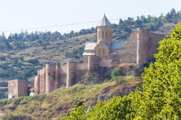 Vista sulla fortezza antica inespugnabile narikala e sulla chiesa di san nicola a tbilisi, georgia