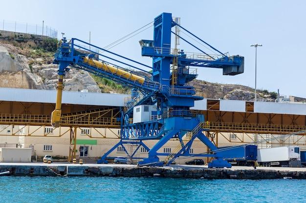 La vista del porto industriale con una grande gru blu che lavora sul molo della città di la valletta.