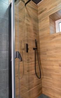 Visualizza in un moderno box doccia con piastrelle in legno e una porta in vetro con miscelatore a parete e soffione doccia su un tubo flessibile