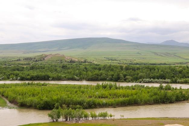Vista sul fiume kura e sulle montagne del caucaso dall'antica città rupestre uplistsikhe, georgia