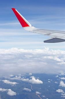Vista della terra, del cielo, della nuvola e dell'ala dell'aeroplano dalla finestra