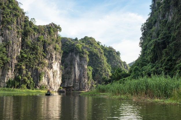 Vista della montagna calcarea nella valle con crociera turistica di sera, fiume ngo dong, ninh binh, baia di halong sulla terra