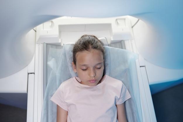 Vista della bambina che tiene gli occhi chiusi prima di sottoporsi all'esame ct