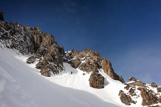 Vista dello snowboarder maschio in casco che cammina lungo il lato della montagna