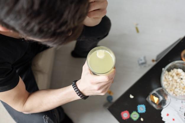 Sopra la vista dell'uomo che beve la cura della sbornia mattina dopo la festa a casa