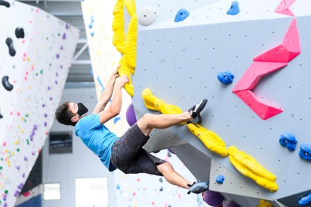Vista di un uomo che indossa una maschera pandemica covid-19 si arrampica su una parete boulder in una palestra di arrampicata seguendo le linee guida sulla distanza sociale per l'esercizio
