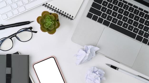 Sopra vista spazio di lavoro disordinato con computer portatile, smartphone, notebook e carta stropicciata.