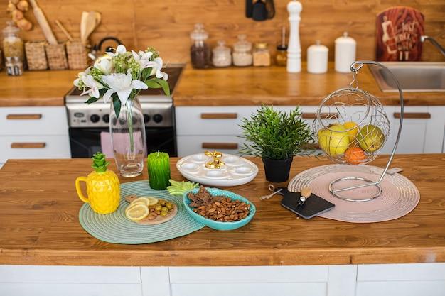 Vista sul bancone della cucina moderna in legno con vari cibi e snack. vaso di gigli e piatto di uova con coniglietto dorato in cima. concetto di pasqua.
