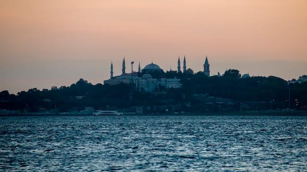 Vista di una moschea e un sacco di vegetazione intorno ad esso di sera, lo stretto del bosforo in primo piano ad istanbul in turchia