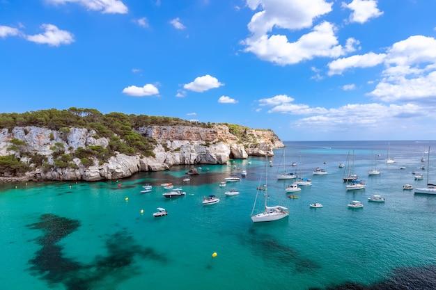 Vista della baia più bella cala macarella dell'isola minorca con acqua color smeraldo e molti yacht sul mare. isole baleari, spagna