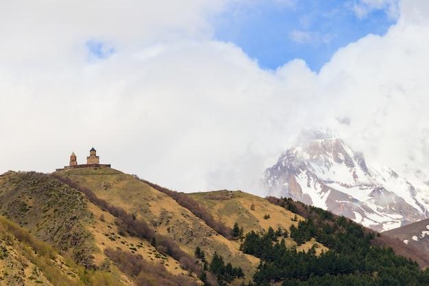 Vista sul monte kazbek e la chiesa della trinità di gergeti nelle montagne caucasiche georgia