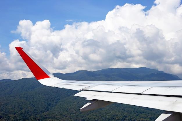 Vista della montagna, del cielo, della nuvola e dell'ala dell'aeroplano dalla finestra