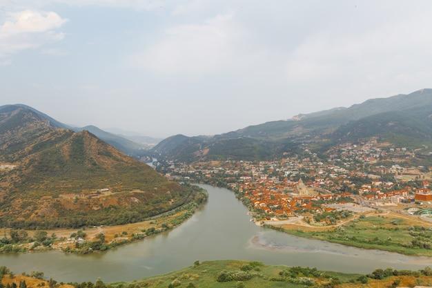 Vista su mtskheta, una delle città più antiche della georgia, dal monastero di jvari. confluenza dei fiumi mtkvari e aragvi con differenza di colore visibile. cielo nuvoloso