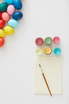 Sopra la vista di multi uova di pasqua colorate con forniture di vernice disposte in una composizione minima su sfondo bianco in studio d'arte, copia dello spazio