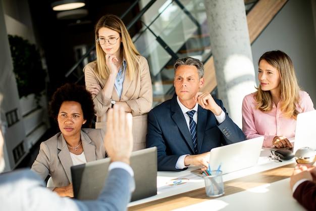 Mostra al gruppo multietnico di uomini d'affari che lavorano insieme e preparano un nuovo progetto sulla riunione in ufficio