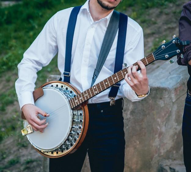 Vista del musicista che suona il banjo in strada