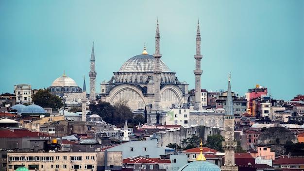 Vista della moschea nuruosmaniye con più edifici residenziali intorno ad esso, tempo nuvoloso a istanbul, turchia