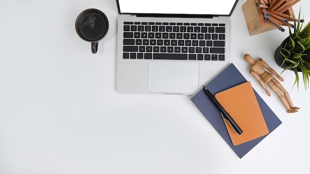 Vista dall'alto della scrivania dell'ufficio con computer portatile, notebook, tazza di caffè e pianta domestica.