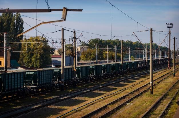 Vista della vecchia ferrovia polverosa con vagoni merci e linee elettriche