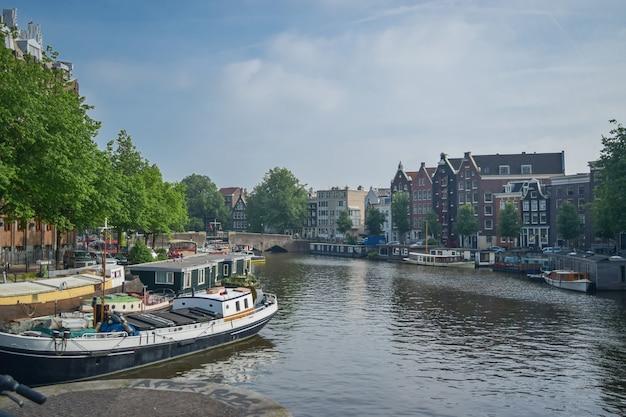 Vista di uno dei canali e delle barche con un vecchio edificio sullo sfondo ad amsterdam, paesi bassi