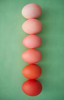 Sopra la vista delle uova di pasqua dipinte in gradiente di riga dal rosso al rosa pastello, copia dello spazio
