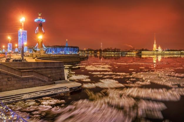 Vista della fortezza di pietro e paolo e delle colonne rostrali a san pietroburgo dal ponte sotto il quale il ghiaccio galleggia sul fiume neva
