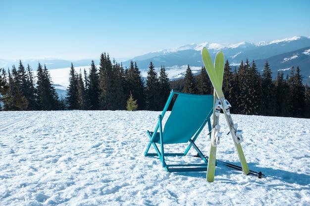 Vista del luogo di riposo con sedia sulla cima del monte alla giornata di sole della stazione sciistica