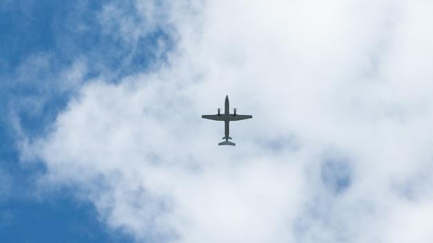 Vista dell'aereo a elica volare basso con cielo blu e nuvole sullo sfondo. aerei passeggeri commerciali in volo sopra la testa. aereo in aria. viaggio in aereo