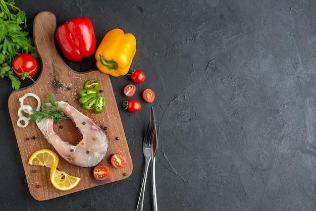 Sopra la vista di pesce crudo e verdure fresche tritate fette di limone spezie su una tavola di legno posate fascio verde sul lato destro su superficie nera angosciata